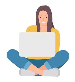 Женщина сидит на полу со скрещенными ногами и использует ноутбук