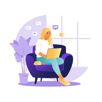 Женщина сидит за столом с ноутбуком и телефоном