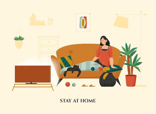 Женщина сидит со своим котом на диване под теплым одеялом на коленях в уютной домашней квартире