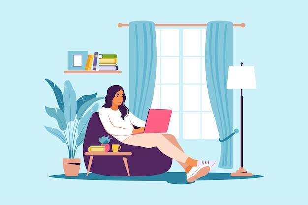일, 공부, 교육, 집에서 일하기 위한 빈백 개념에 노트북을 들고 앉아 있는 여성.