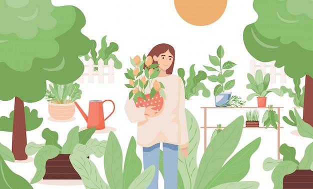 Женщина стоя в саде и держа бак с иллюстрацией дерева лимона. farmgirl садоводство.