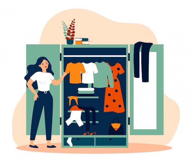 Женщина стоит возле открытого шкафа и смотрит на платья