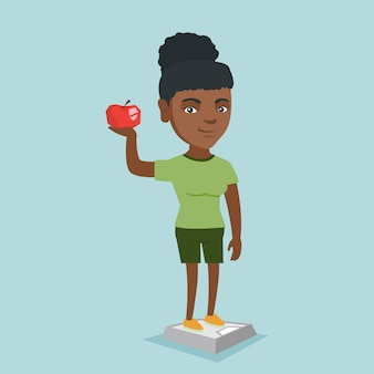 Woman standing on scale and holding apple in hand.