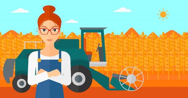 Женщина стоя с зернокомбайном на предпосылке.