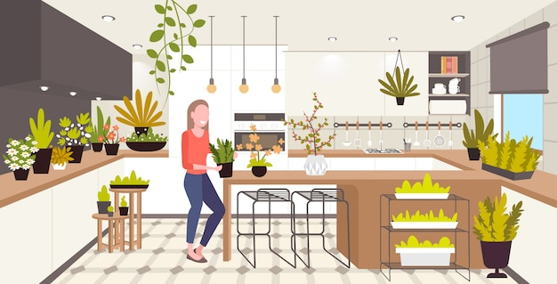 Woman taking care of houseplants girl enjoying ecology hobby stay home lifestyle kitchen interior