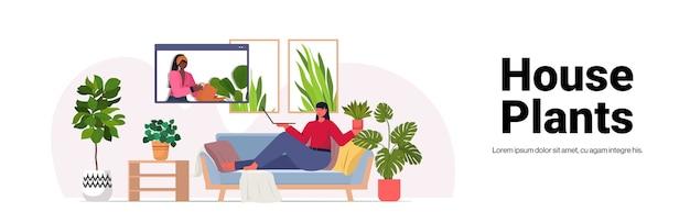 観葉植物の世話をしている女性主婦がビデオ通話中にウェブブラウザウィンドウで友人と話し合っている水平コピースペース