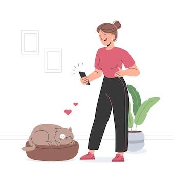 スマートフォンで猫の写真を撮る女性