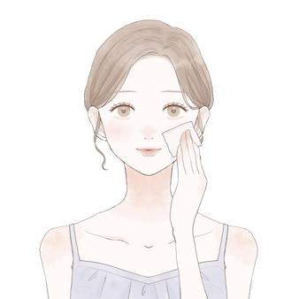 一枚の紙で顔の皮脂を取る女性。白い背景に。