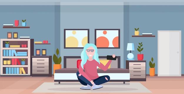 ベッドモダンなベッドルームのインテリア女性漫画のキャラクター全長水平近くの床に座っているスマートフォンのカメラの女の子でselfie写真を撮る女性