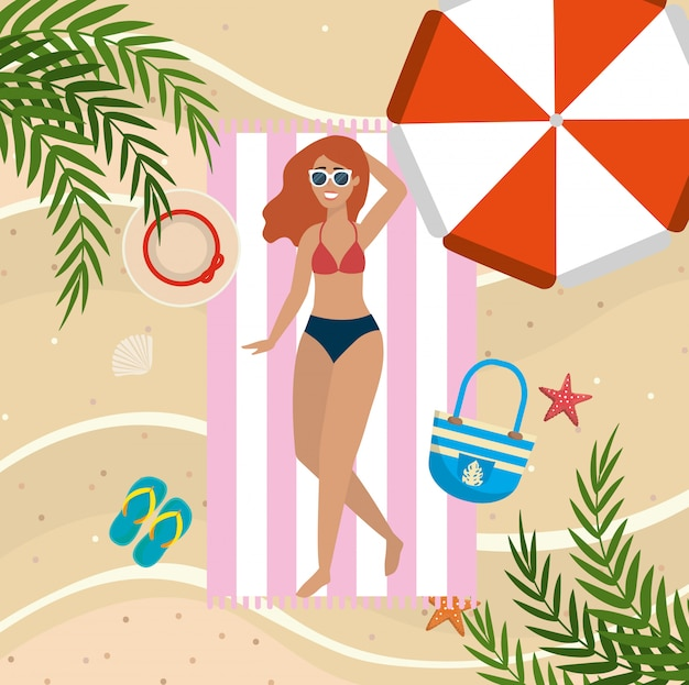 Woman taking sun in the towel with umbrella and sunglasses