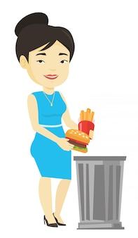 Женщина бросает нездоровую пищу.