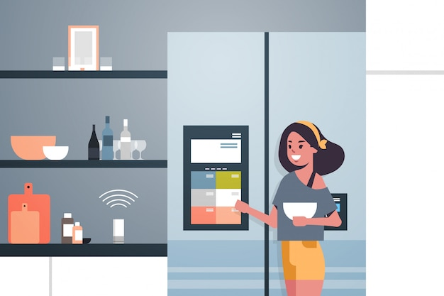 Woman touching refrigerator screen with smart speaker voice recognition