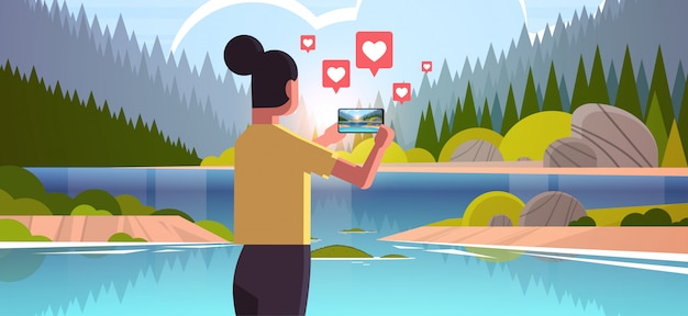 Woman traveler photographing beautiful nature on smartphone camera traveling