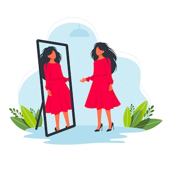 Woman trying on a beautiful red dress in the store in front of the mirror. try on fashion clothes concept. fitting clothes.