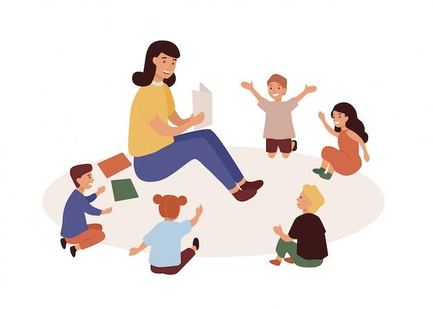 Woman tutor and preschoolers reading in nursery.