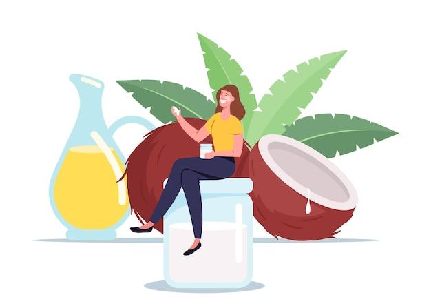 여자는 코코넛 오일 개념을 사용합니다. 녹색 잎을 가진 코코넛 근처의 거대한 유리 항아리에 앉아 있는 작은 여성 캐릭터
