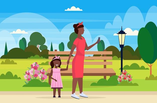 작은 아이 딸과 함께 도시 공원을 걷는 동안 핸드폰을 사용하는 여자는 어머니 스마트 폰 중독 개념 풍경 배경 전체 길이의 관심을 원하는