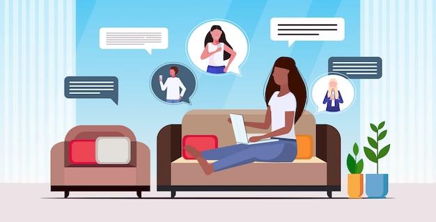Женщина с помощью портативного компьютера в чате приложение социальной сети речи пузырь пузырь связи концепция