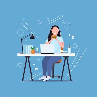 ハンバーガーファーストフードを食べるラップトップを使用している女性不健康なライフスタイルコンセプト太りすぎの女の子フリーランサー職場フラットフラット長さで座っています。