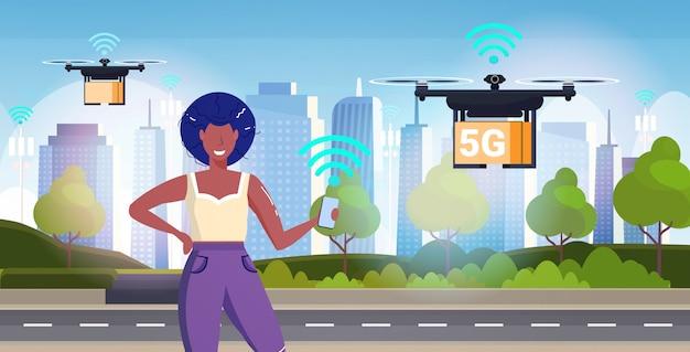 スマートフォンを使用してクワッドコプター5 g第5世代のインターネット接続エクスプレスドローン配信コンセプトを使用して女性