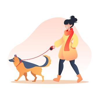 秋の公園で犬を散歩する女性、ペットケアのコンセプト