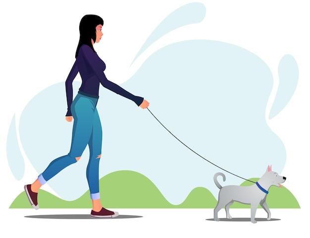 朝のプレミアムで公園で彼女の犬を歩く女性