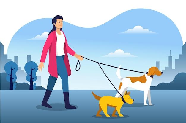 彼女の犬と一緒に公園を歩いている女性