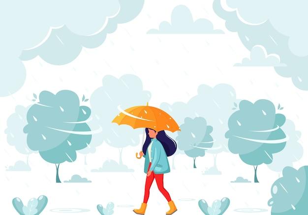 雨の間に傘の下を歩く女性。秋の雨。秋の野外活動。