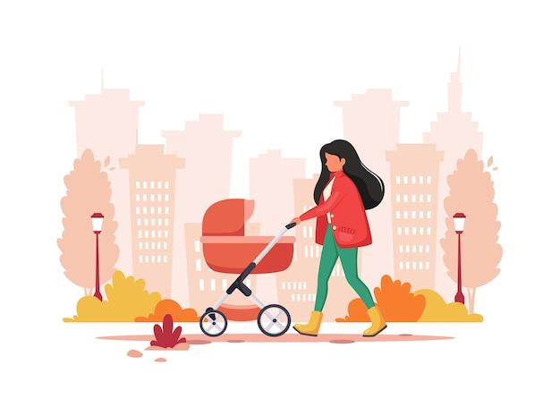 秋に乳母車で歩く女性。アウトドアアクティビティのコンセプト。