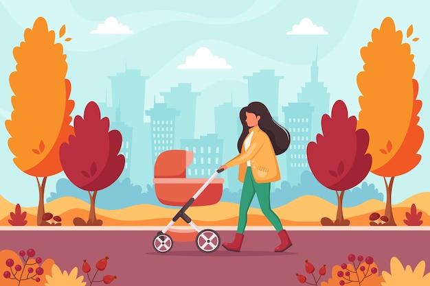 가을 공원에서 유모차와 함께 걷는 여자