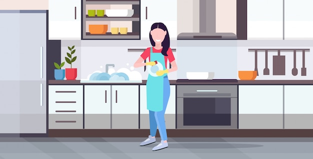 Woman washing dishes housewife wiping plates with towel dishwashing concept girl in apron doing housework modern kitchen interior horizontal flat full length