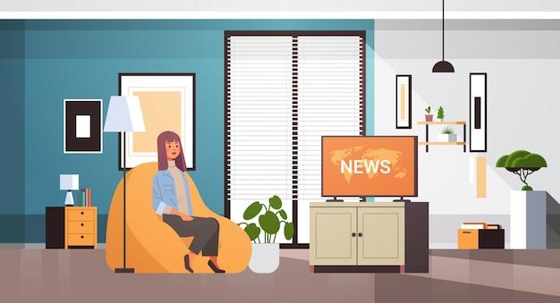 肘掛け椅子のリビングルームのインテリアに座っているテレビ少女のテレビ毎日ニュース番組を見ている女性