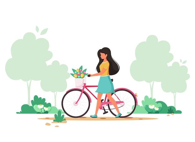 봄 공원에서 바구니에 꽃과 자전거를 가진 여자