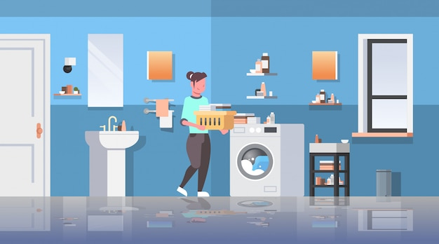 家事モダンなバスルームのインテリアの漫画のキャラクターをしている洗濯機主婦の近くに立っている服のバスケットを持つ女性