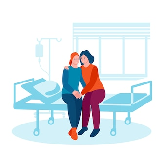 A woman with cancer sits on a bed in a hospital a friend hugs supports