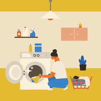 服と洗濯機を持つ女性。ハウスキーピングのコンセプト。