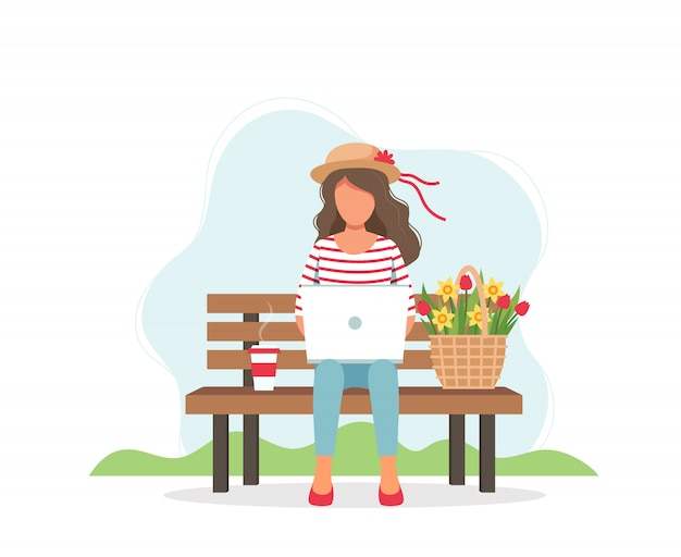 Woman with laptop sitting on the bench and spring flowers in basket.