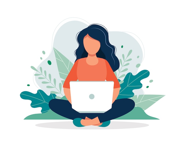 Woman with laptop sitting in nature and leaves