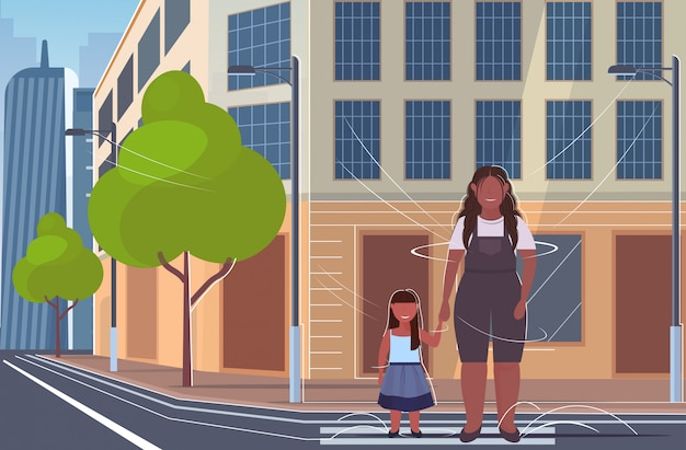 Woman with little child standing on crosswalk    mother and daughter walking outdoor city street cityscape background full length  horizontal