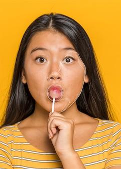 Donna con lecca-lecca con linee sul viso