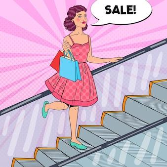 エスカレーターで買い物袋を持つ女性