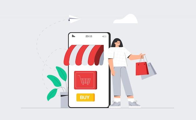 大きな電話の隣に立ってオンラインショッピングの買い物袋を持つ女性。