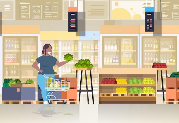 野菜や果物のコンセプトの女の子のスーパーマーケットの顧客を選択するショッピングトロリーカートを持つ女性
