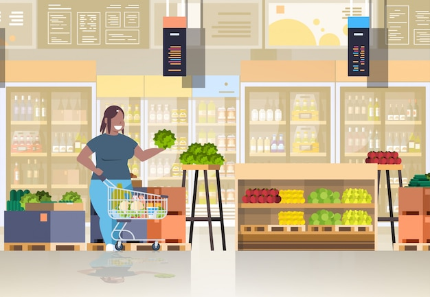 Woman with shopping trolley cart choosing vegetables and fruits  concept   girl supermarket customer