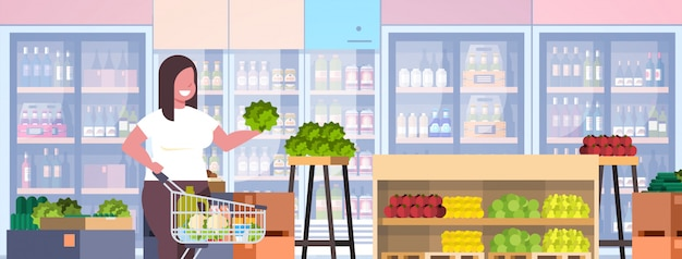 Woman with shopping trolley cart choosing vegetables and fruits weight loss concept