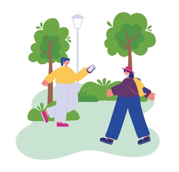 スマートフォンと帽子と公園を歩いてバックパックを持つ少女と女性