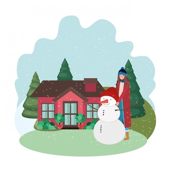 Woman with snowman and house in winter