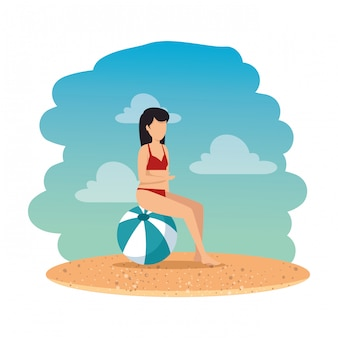 Woman with swimsuit seated in balloon on the beach