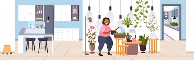 실내 식물을 돌보는 관엽 식물을 돌보는 물을 수있는 여자는 가정 생활을 유지