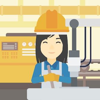 Woman working on industrial drilling machine.